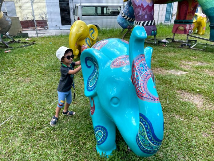 Toddler plays with elephant sculpture